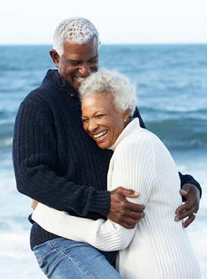 A couple embraces after getting dentures