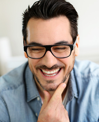 A man with dental crowns smiles for the camera