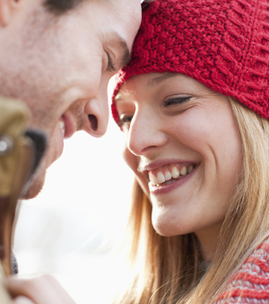 A couple who has had cosmetic dental procedures smiles at one another.